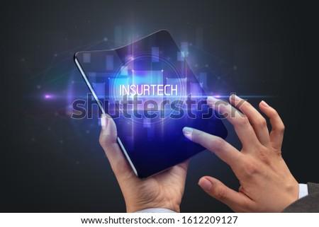 Businessman holding a foldable smartphone, new technology concept Stock photo © ra2studio