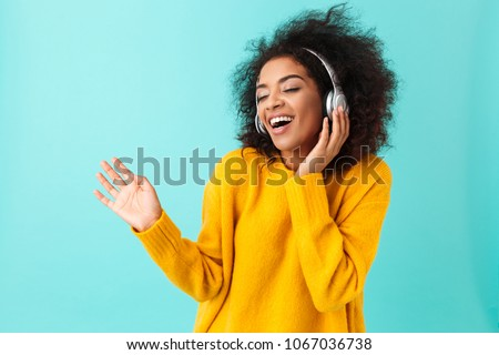 Image of pleased young woman smiling and using headphones while sitting Stock photo © deandrobot