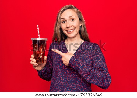 Image of excited blonde woman drinking soda and showing thumb up Stock photo © deandrobot