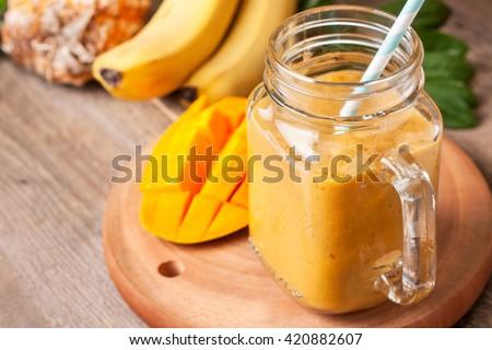 Mango smoothie in a glass Mason jar and mango on the old wooden background. Mango shake. Tropical fr Stock photo © galitskaya