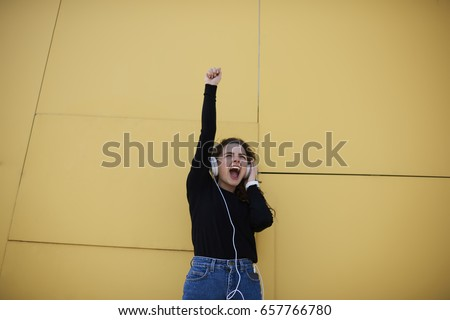Stock photo: Good looking woman using her headphones while standing against a white background