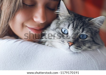 Young woman holding beautiful tabby looking up cat, relaxed on g stock photo © HASLOO