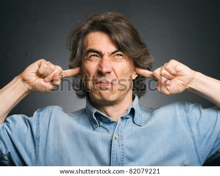 Stressed young woman covering his ears, grimacing and gesturing  Stock photo © dacasdo