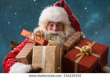 Photo of happy Santa Claus outdoors in snowfall carrying gifts t Stock photo © HASLOO