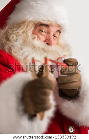 Portrait of happy Santa Claus aiming christmas gift with slingsh Stock photo © HASLOO