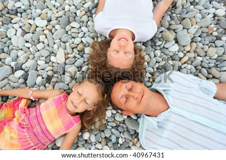 Stock photo: Happy family with little girl lying on stony beach, closed eyes,