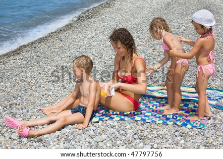 young woman and three children smear each other backs with cream Stock photo © Paha_L