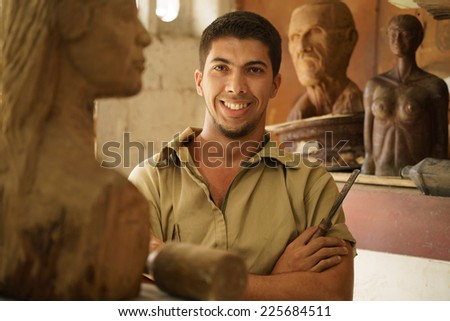 portrait happy artist man working with wood sculpture in atelier stock photo © diego_cervo