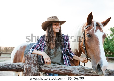 cheerful beautiful young woman cowgirl with her horse on ranch stock photo © deandrobot