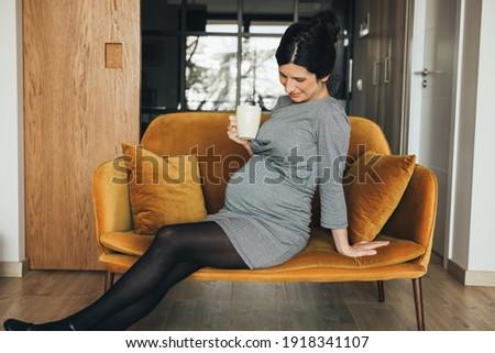 elegant brunette businesswoman in black dress sitting on chair stock photo © deandrobot