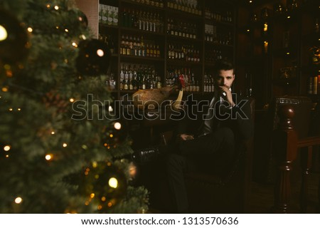attractive man wearing a black tuxedo sitting on wooden chair Stock photo © feedough