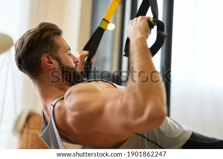 Handsome young man with strong arms hanging on gymnastic rings Stock photo © Kzenon