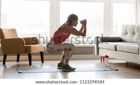 Side view of Serious sports woman doing exercise with dumbbells Stock photo © deandrobot