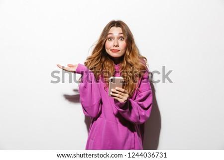 Portrait of surprised woman 20s wearing sweatshirt using cell ph Stock photo © deandrobot