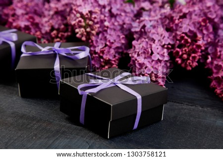 Black small gift boxes wrapped purple ribbon with natural lilac.  Stock photo © Illia