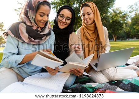 Happy young arabian women students writing in copybooks in park outdoors. Stock photo © deandrobot