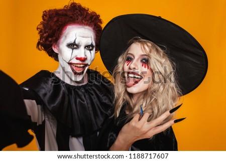 Joyful clown man 20s wearing black costume and halloween makeup  Stock photo © deandrobot