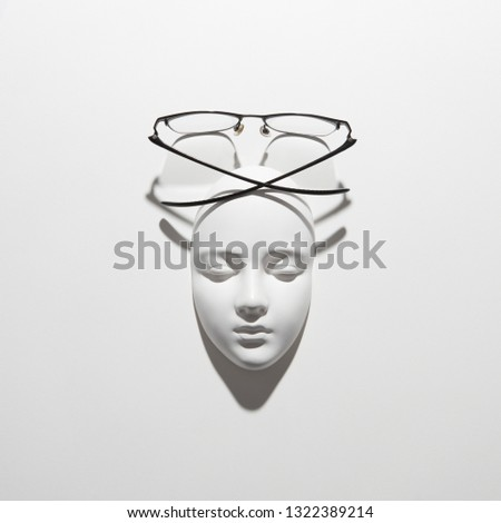 Gypsum face mask with elegant glasses above it on a white background with soft long shadows, copy sp Stock photo © artjazz