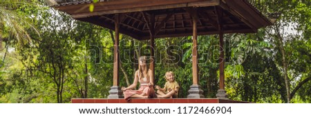 Mom and son meditate practicing yoga in the traditional balinesse gazebo Stock photo © galitskaya