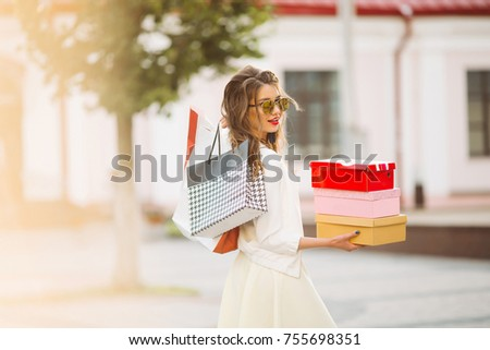 Smiling woman holding colorful boxes with shoes after shopping. Stock photo © studiolucky