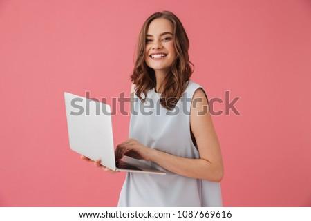 Piękna kobieta odizolowany różowy za pomocą laptopa komputera wpisując Zdjęcia stock © deandrobot