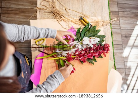 female florist is decorating beautiful bouquet from fresh natural roses step by step at the table wi stock photo © artjazz