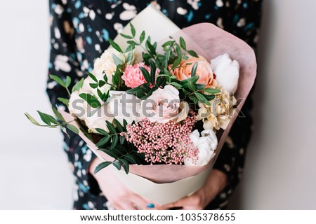 Young girl hold fresh natural floral bouquet with roses, eryngium and green leaves. Concept of Mothe Stock photo © artjazz