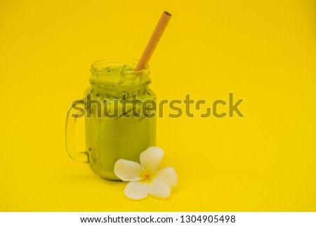 Green tea latte with ice in mason jar and straw on yellow background. Homemade Iced Matcha Latte Tea Foto stock © galitskaya