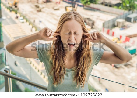 A young woman by the window annoyed by the building works outside, wired soundproof wireless headpho Stock photo © galitskaya