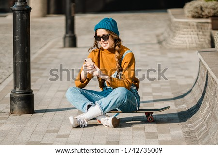 Young smart student female in casual clothes. Woman sitting on grass ground, working on laptop pc co Stock fotó © galitskaya