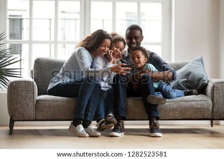 Family of four having fun on the sofa at home play video game stock fotó © Lopolo
