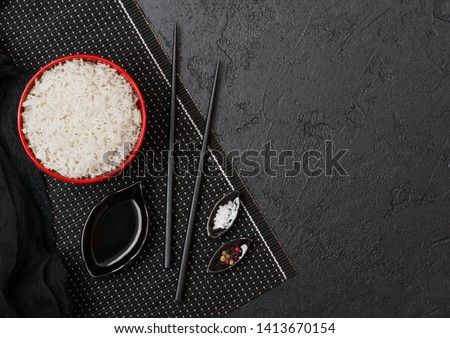 Black bowl with boiled organic basmati jasmine rice with black chopsticks and sweet soy sauce on bam Stock photo © DenisMArt