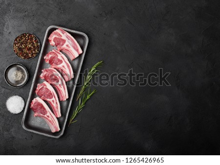 Fresh raw butchers lamb beef cutlets in plastic tray with vintage meat hatchets on black background. Stock photo © DenisMArt