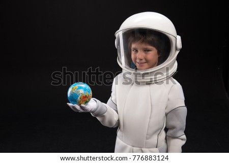 Cosmonaut concept. Waist up portrait of positive little boy wearing white armor and helmet is standi Stock photo © galitskaya