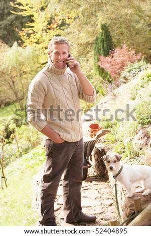 Stock photo: Man Outdoors On Mobile Phone With Dog Whilst On Break From Garde
