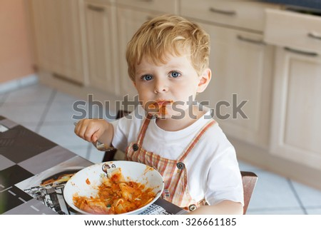 Adorable little boy eating pasta indoor. Toddler child in domestic kitchen or in nursery. Cute kid a Stock photo © Lopolo