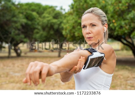 Cheerful aged woman with outstretched arms looking at her husband with camera Stock photo © pressmaster
