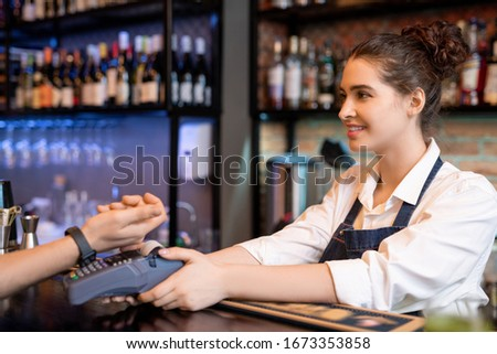Happy young barista looking at client paying for drink by contactless payment Stock photo © pressmaster