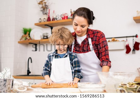 Young woman in apron standing close to her little son rolling homemade dough Stock photo © pressmaster