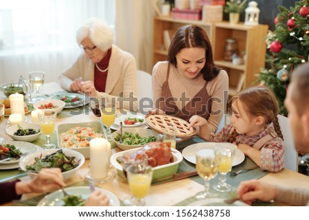 Young mother offering piece of homemade pie to her little daughter by dinner Stock photo © pressmaster