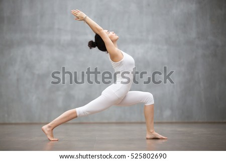 Young female standing on hands in one of yoga positions in front of touchpad Stock photo © pressmaster