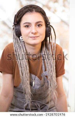 Pretty young restful woman with dreadlocks listening to music in headphones Stock photo © pressmaster