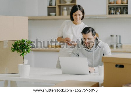 Photo of newlywed couple think about furnishing new bought house, search some ideas in internet on m Stock photo © vkstudio