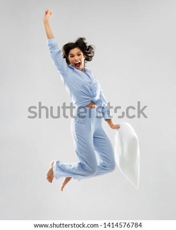 happy woman in blue pajama jumping high Stock photo © dolgachov