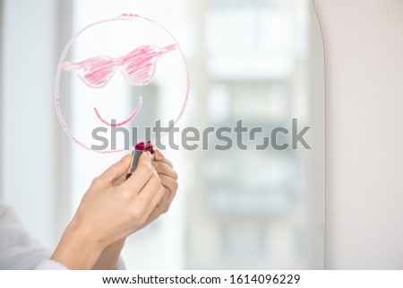 Hand of young female with crimson lipstick drawing funny face showing tongue Stock photo © pressmaster
