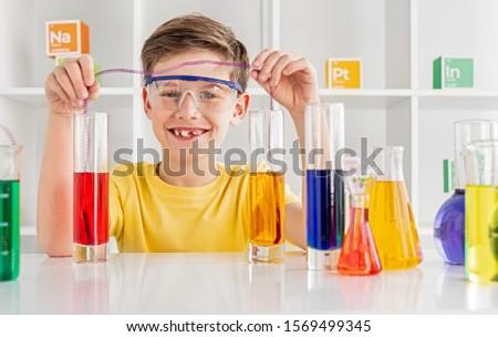 Mądry mały naukowiec chemicznych próba mikroskopem Zdjęcia stock © pressmaster