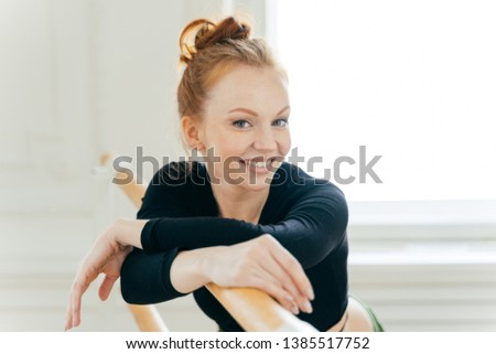 Fitness female with red combed hair, wears special clothes, practices ballet on barre in dancing stu Stock photo © vkstudio