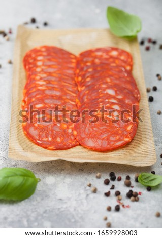 Dry-cured chorizo sausage slices with a distinctive spicy paprika flavour with basil and pepper on w Stock photo © DenisMArt