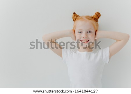 Indoor shot of glad smiling girl covers ears with hands, ignores noise, has two ginger buns, freckle Stock photo © vkstudio