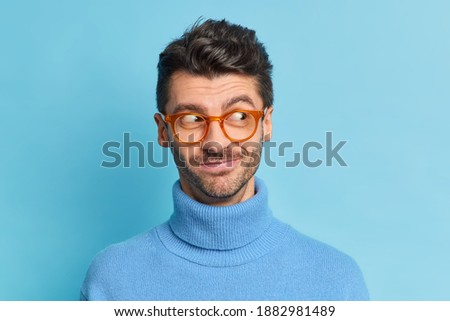 Pleased attractive man with stubble, wears transparent glasses, fashionable hat and shirt, writes wi Stock photo © vkstudio